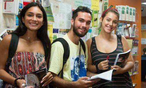 3 students holding student planners