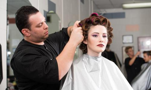 male cosmetology student working on model's hair