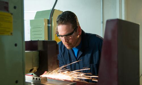 man working on machine with sparks