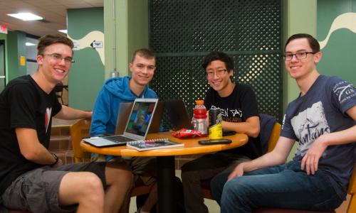 four male students sitting around table