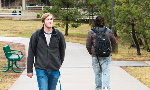 front and back of male students walking outside
