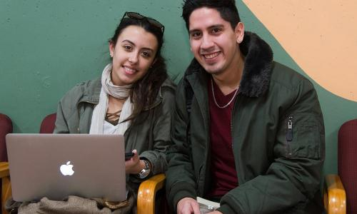 female student with laptop seated next to male student in jacket