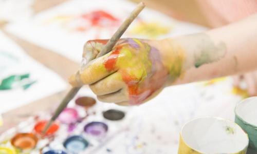 child's hand painting watercolor