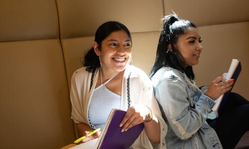 two females students sitting back to back