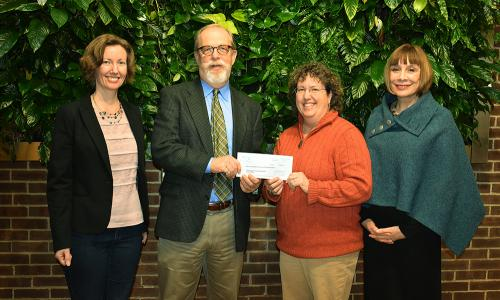four people with check presentation