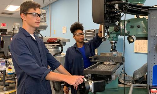 male and female hs students on advanced manufacturing machines