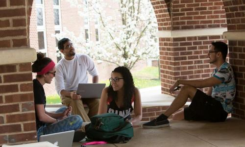 students sitting outside under under arches