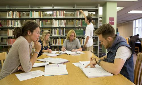 students studying around table in library