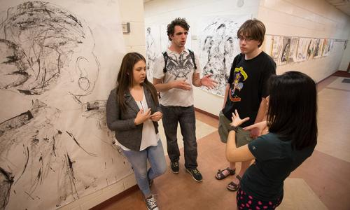 four students next to murals in arts building
