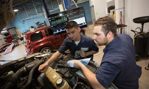 2 males students working on car