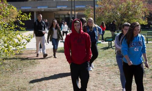 group of students in sweatshirts walking outside
