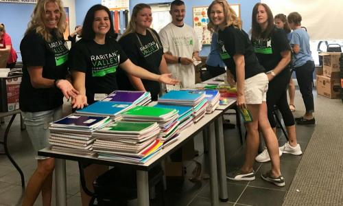 students around table of collected school supplies