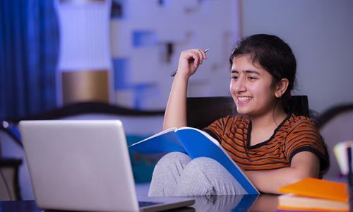 teen girl with orange and black striped shirt on laptop