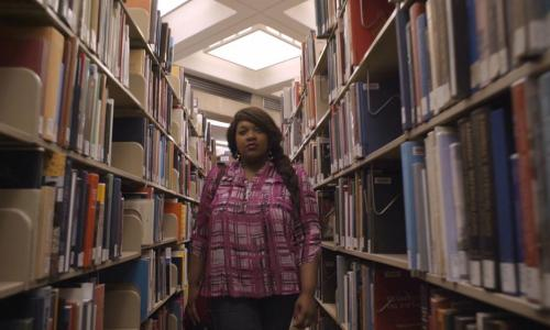 young woman walking between library shelves