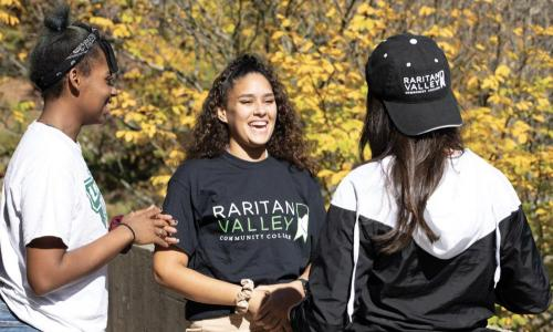3 girls outside with girl in middle wearing rvcc tshirt