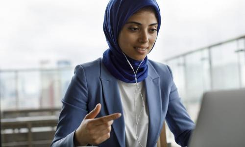 young woman in blue blazer on laptop